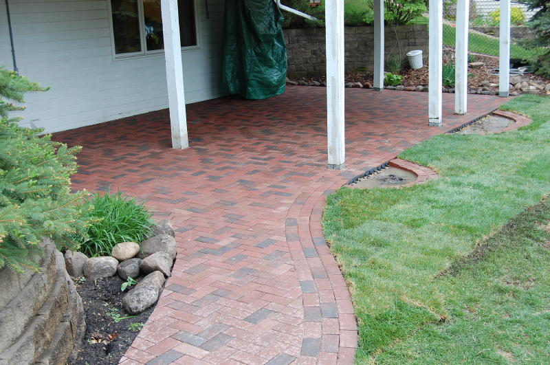 Photo of brick stone paver patio area in herring bone pattern with triple running bond border.