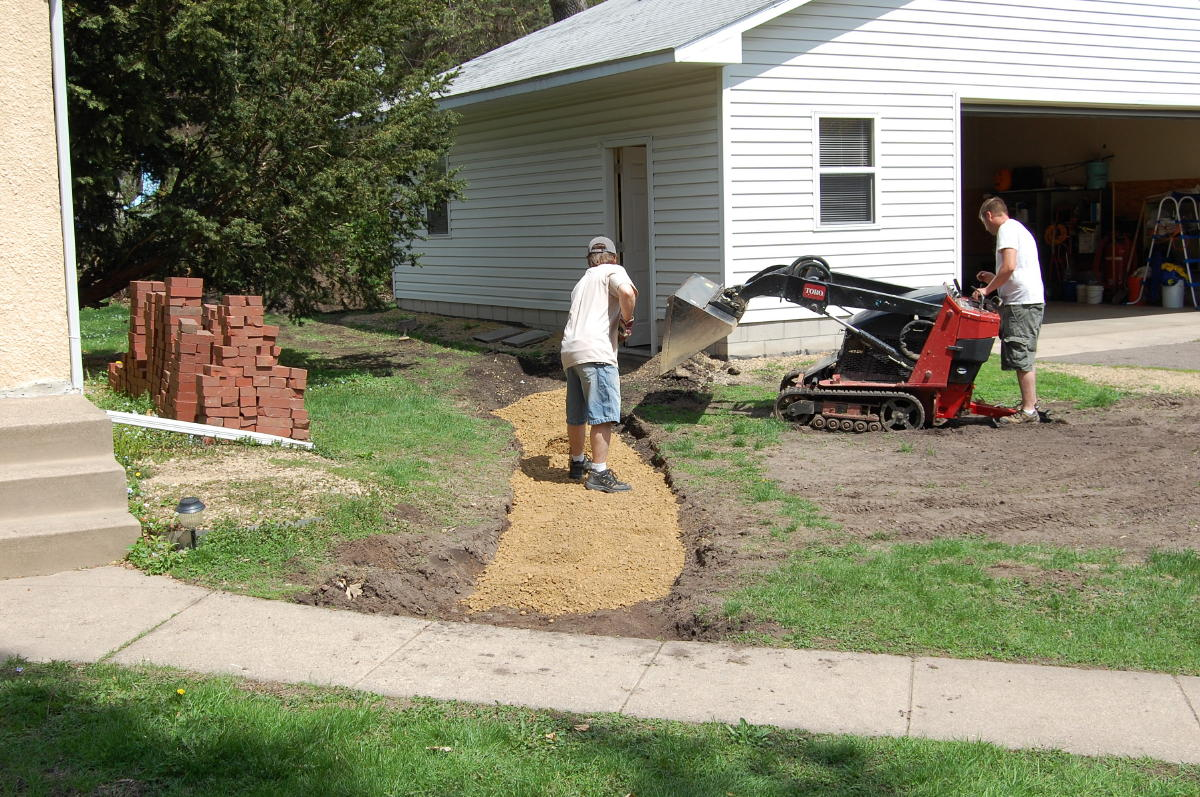 image of compact loader installing paver base to sidewalk